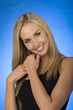 Studio shot of blonde fashion model against blue background.