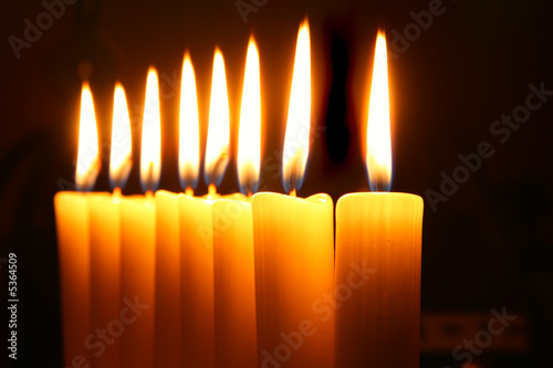 Eight burning candles over black background