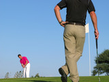 Golfer watching his opponent take a long difficult putt. poster