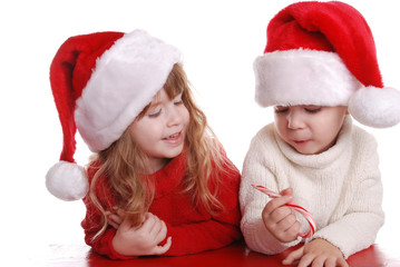 A brother and sister eating a candy cane