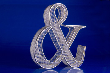 Wire mesh ampersand symbol on a blue background.