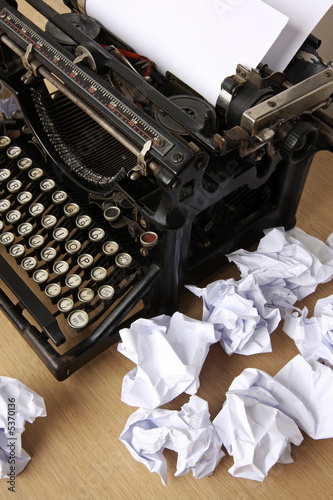 Typewriter with paper scattered - conceptual image
