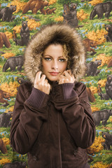 Caucasian young adult woman wearing coat with fur hood.