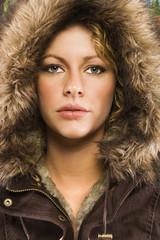 Caucasian young adult woman wearing fur hood.