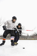 Two boys in ice hockey uniforms playing hockey on ice rink.