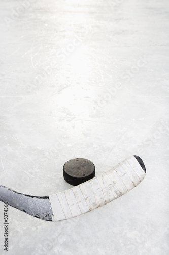 Close up of ice hockey stick on ice rink.