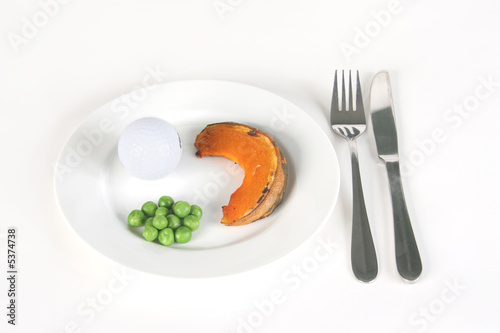 A golf ball and vegetables on a plate