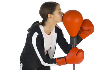 Young beauty with boxing gloves. Kissing punch bag.