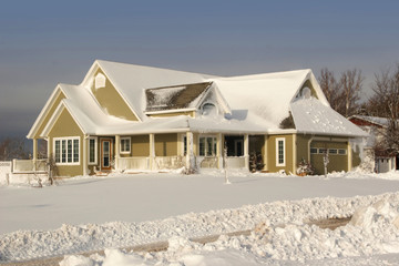 Modern residential home covered with newly fallen snow.