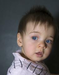 Baby mit blauen Augen riskiert einen neugierigen Seitenblick
