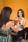 African American women handing item to sales clerk in boutique. poster