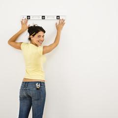 Woman leveling wall.