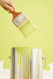 Caucasian female hand holding paintbrush over paint can. poster
