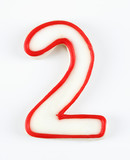 Sugar cookie in the shape of a number two outlined in red icing. poster