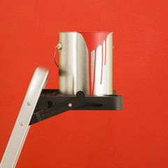 Still life of paint can on step ladder in front of red wall.