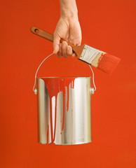 Caucasian female hand and leg holding paint can and paintbrush.