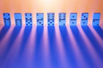 Row of dominos with light casting long shadows.