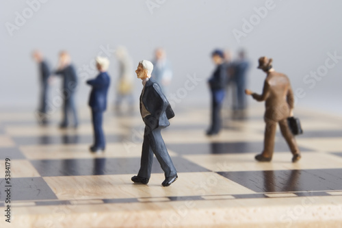 Business figurines placed on chessboard  - 5384179