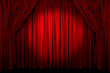 Large red curtain with spot light and fading into dark.