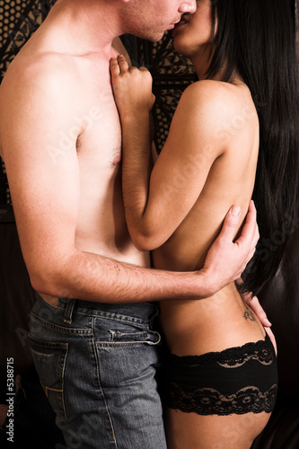 Multi-ethnic couple in passionate embrace and undressing