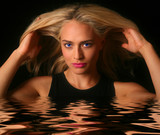 Beautiful Woman Emerging from Rippling Water on Black Background poster