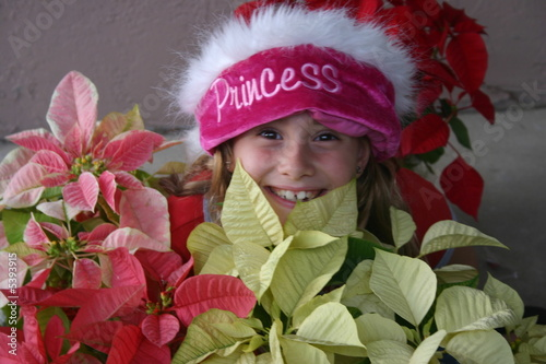 young girl santa hiding in poinsetta