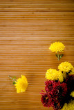 Sparsed yellow and magenta flowerd on wooden background poster