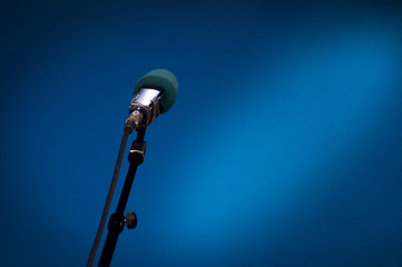Microphone on the stage with the blue background and lights