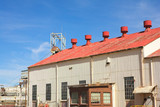 Corrugated iron building with red roof on mine premises  poster