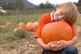 Boy holding a pumpkin in a pumpkin patch poster