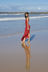 Beautiful girl in red dress on the beach