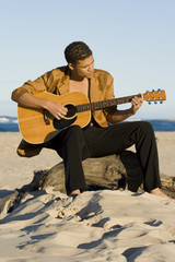 Young man playing his guitar on the beach