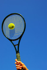Tennis player swinging and hitting the ball
