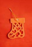 Orange felt Christmas tree decoration on an orange background. poster