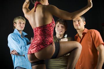 Three men standing in front of dancing woman in dark room