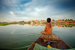 Cambodian boy on prow of small boat overlooking lake - 5419510