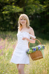 Sexy girl walk with basket on meadow