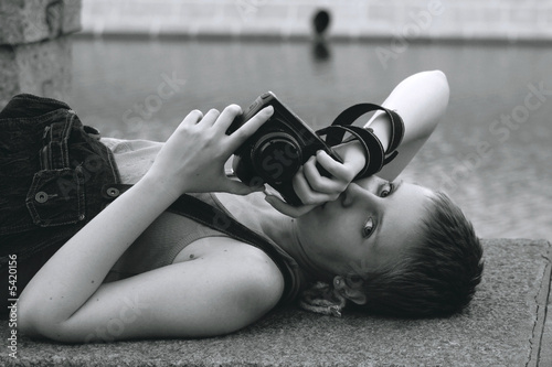 Young sexy woman with the camera lying near the river © Saite