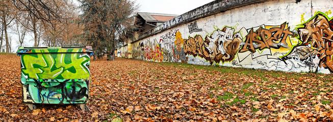 Poubelle et graffitis dans un jardin public en automne