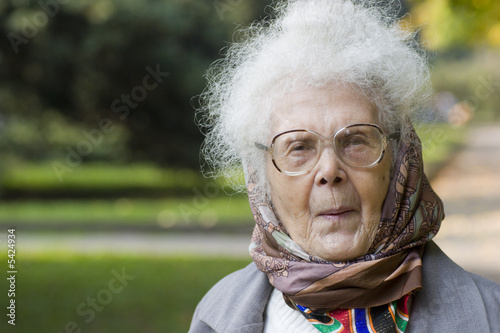 Portrait of Old lady wearing glasses in the park