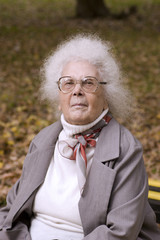 Old lady in the autumn park wearing glasses looking at you