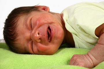 Adorable newborn crying, laying on blanket.
