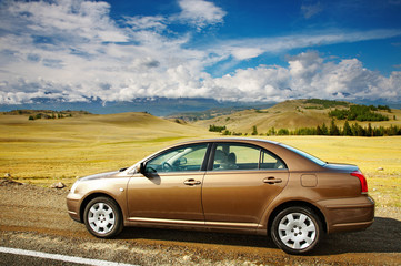 Car at the roadside and mountains on background
