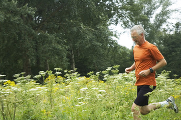 Senior man is running through a field of flowers.