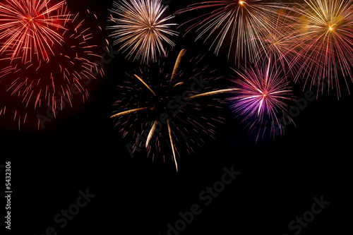 Multiple brightly coloured fireworks exploding