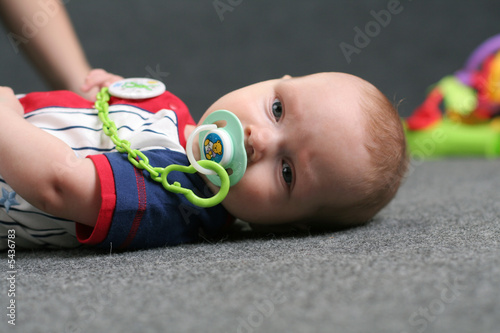 Cute small kid lays on the grey background