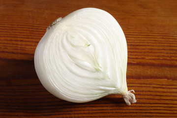 Half an onion on old wooden board