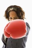 Businesswoman wearing boxing gloves punching. poster