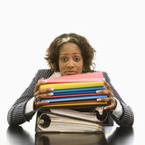 Businesswoman resting head on large stack of books and files. poster