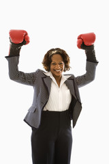 Businesswoman wearing boxing gloves holding arms up.